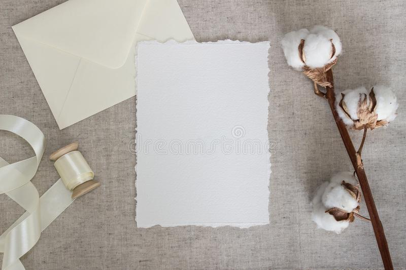 Torn edge paper card on linen cloth with cotton flowers and silk ribbon. Wedding stationery mockup. Calligraphy template royalty free stock photo