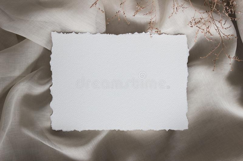 Torn edge paper card on linen cloth with tiny flowers, closup. Wedding stationery mockup. Calligraphy template royalty free stock photo