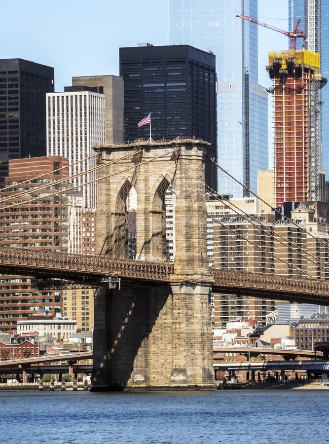 Torn för Brooklyn bro med USA flagga-, Manhattan byggnadsbakgrund tidigt på morgonen med blå himmel och solsken fotografering för bildbyråer