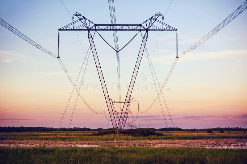 Torn för hög spänning för kontur elektriskt på solnedgångtid royaltyfria foton