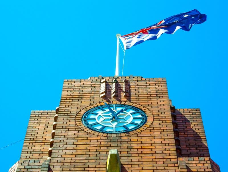 Torn för klocka för röd tegelsten för närbild med den australiska flaggan på det bästa anseendet mot solskenljuset arkivfoto