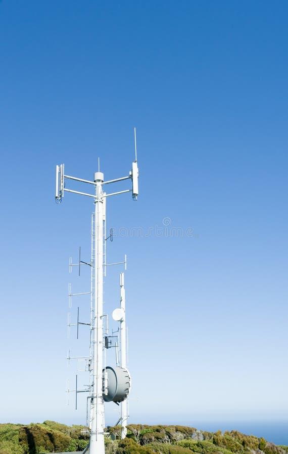 Torn för mobila kommunikationer mot klar blå himmel fotografering för bildbyråer