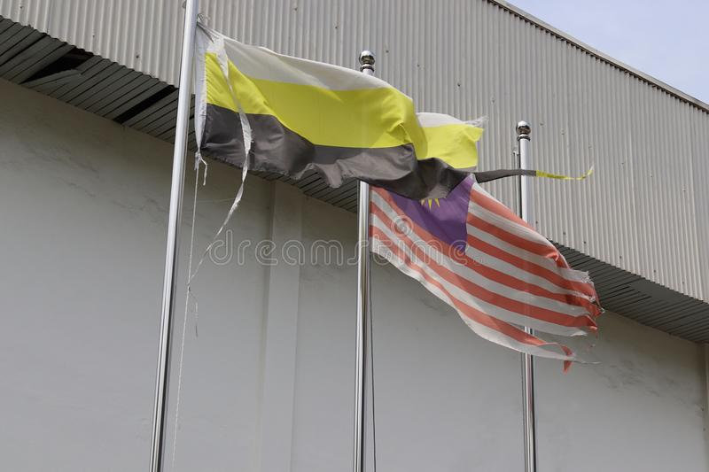Torn And Faded Flags Fluttering In The Wind. Torn and faded Malaysian and the Perak state flag mounted on a steel flagpole fluttering in the wind stock photography