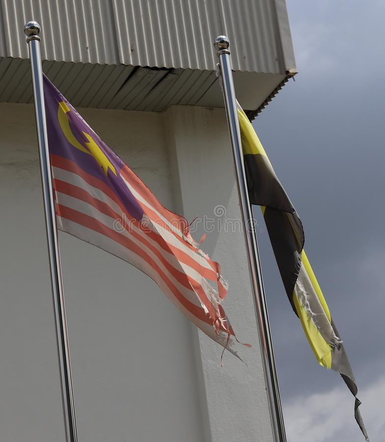 Torn And Faded Flags. Torn and faded Malaysian and the Perak state flag mounted on a steel flagpole royalty free stock photography