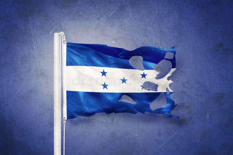 Torn flag of Honduras flying against grunge background.  stock images