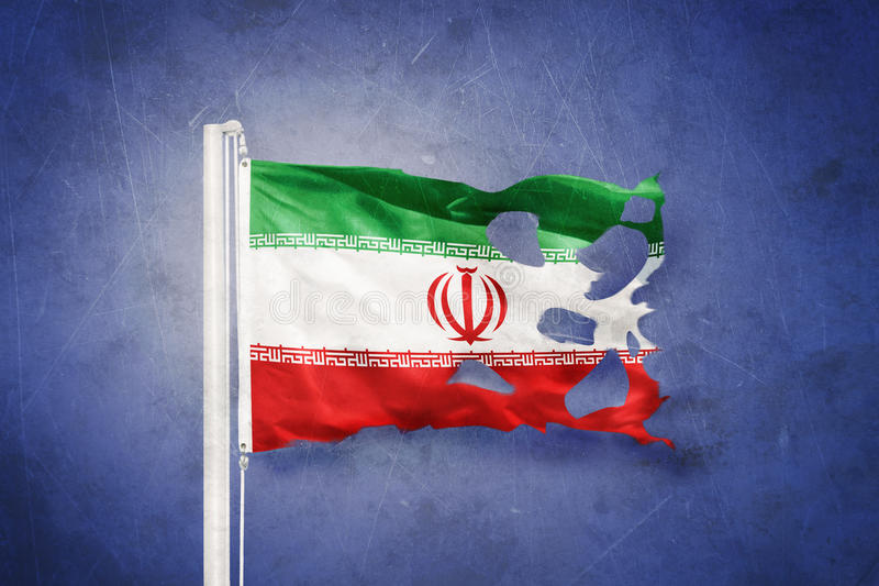 Torn flag of Iran flying against grunge background.  royalty free stock photos
