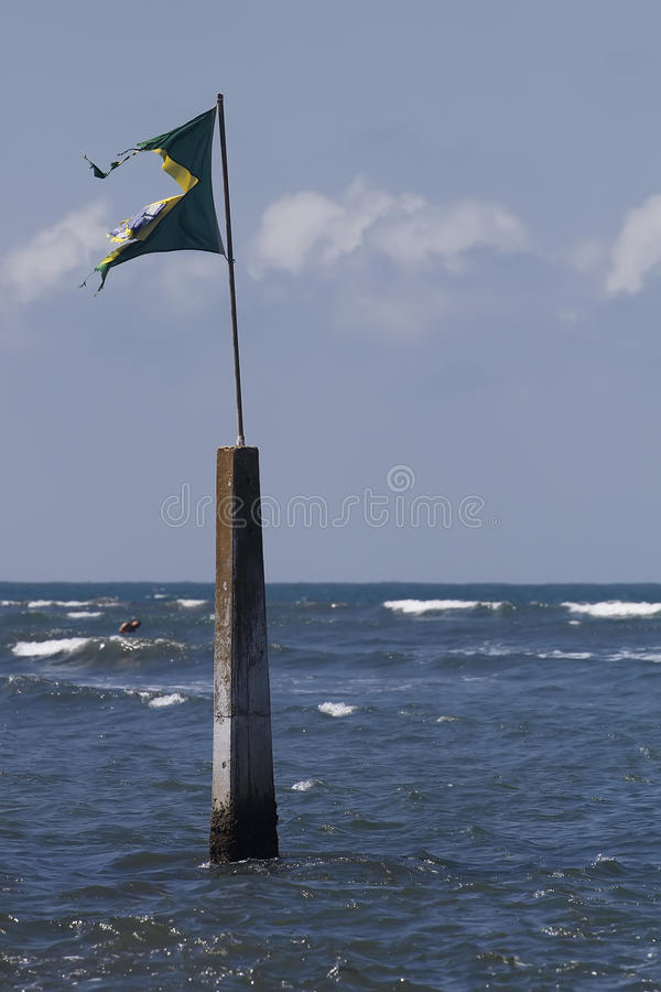 Torn Flag On Marker In Sea Stock Images