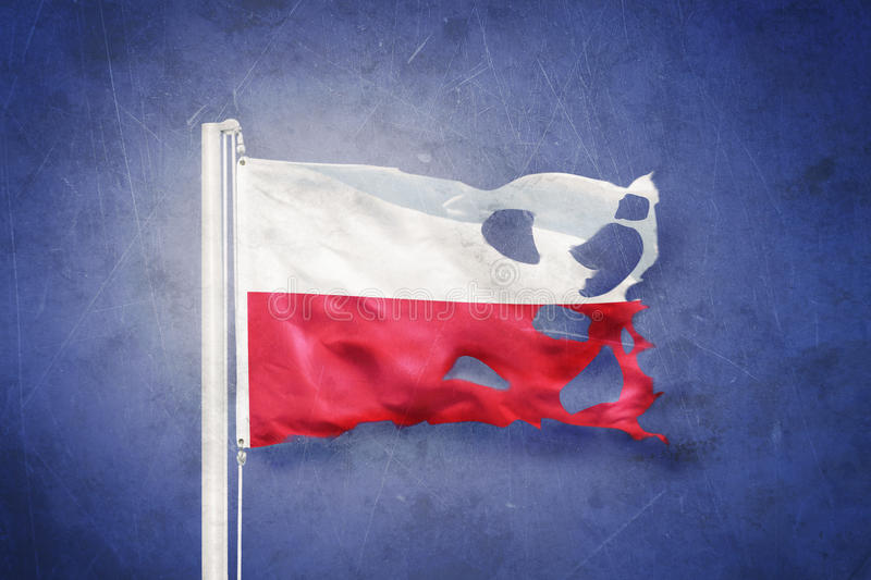 Torn flag of Poland flying against grunge background stock photos