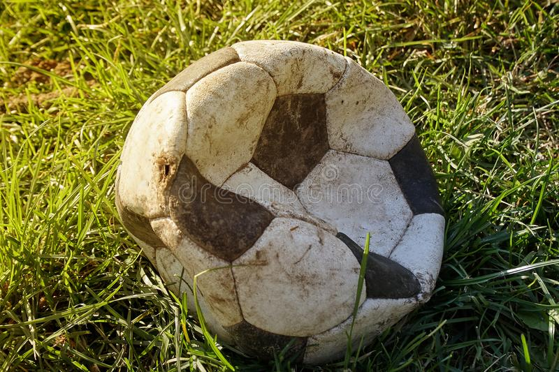 Torn football on the grass lawn. Soccer ball skin torn on the field, but still in use for play stock photo