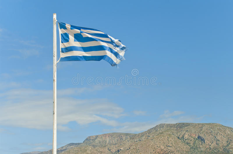 Torn greek flag on flag-post against blue sky royalty free stock photos