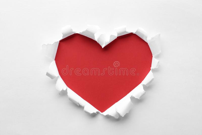 Torn heart shaped hole in white paper. Red space for text stock photos