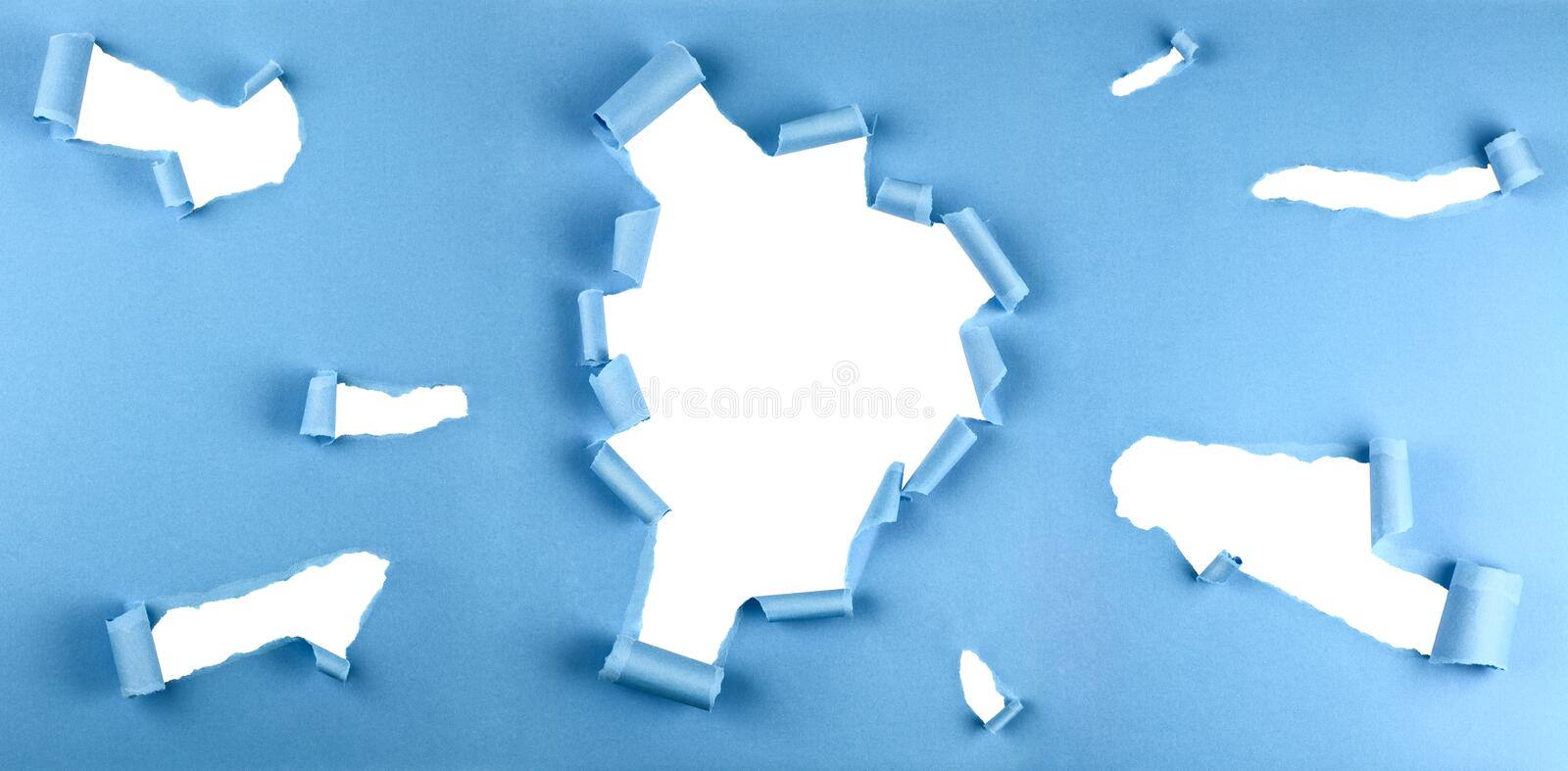 Torn holes in blue paper royalty free stock photography