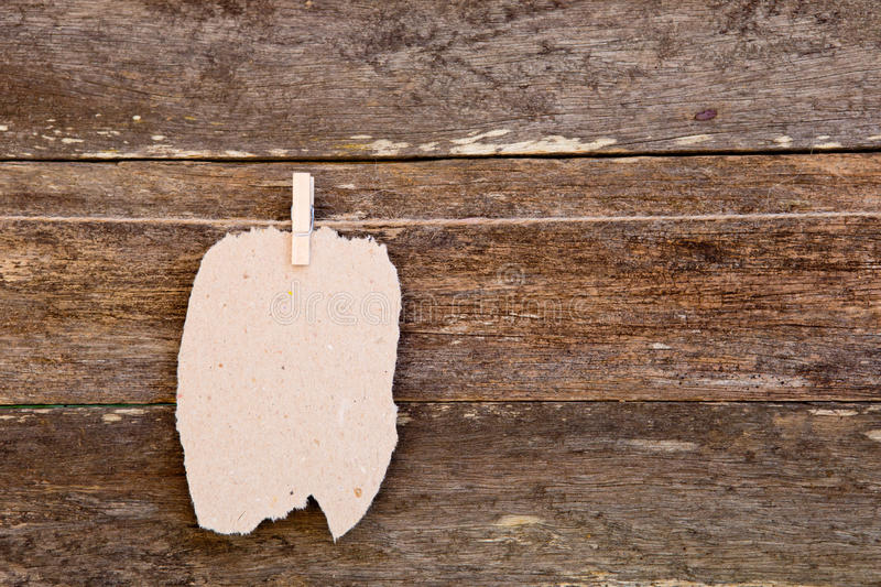 Torn homemade Paper - cardboard label hanging on clothespin against old wooden background. Torn homemade Paper - cardboard label hanging on clothespin against royalty free stock photos
