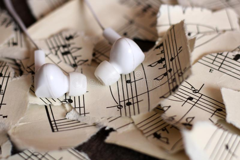 Torn musical notes, pieces of paper, white vacuum headphones royalty free stock photo