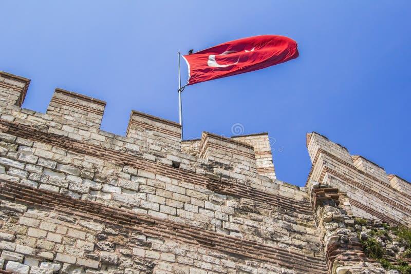 Torn och väggar av fästningen Yedikule med den turkiska flaggan royaltyfri foto