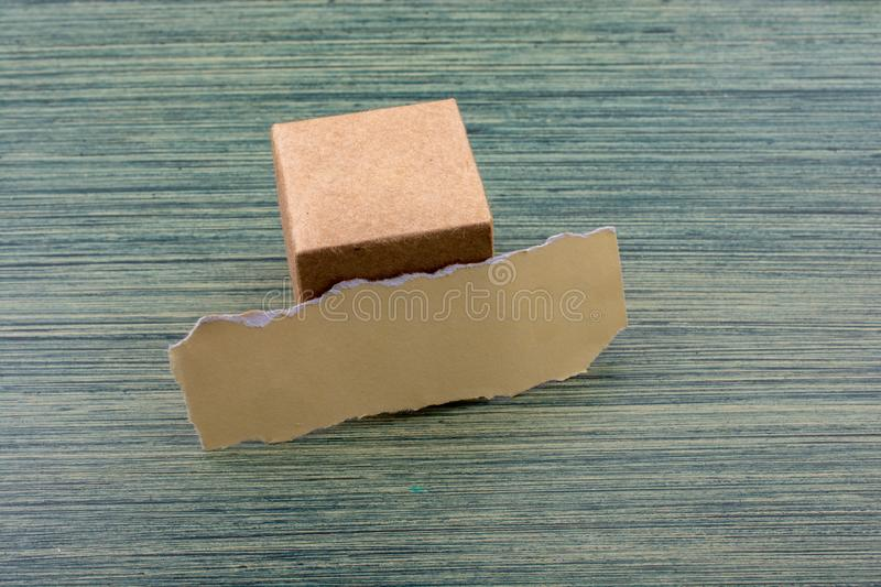Torn paper and a paper box cube. On wooden texture stock photos
