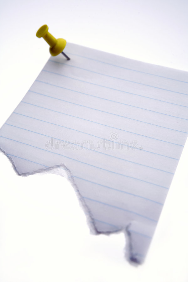 Torn paper note. Torn, blank piece of notebook paper, held in place by a pushpin.; isolated on white stock photo