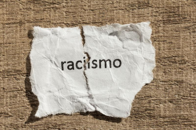 Torn paper written racismo, portuguese and spanish word for racism, over wood table. Concept of old and abandoned idea or royalty free stock photos