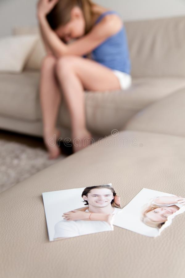 Torn photo of happy couple, crying desperate woman at background stock photo