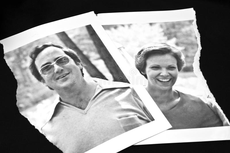 Torn Photograph/Divorce Concept. An old black and white photograph of two people in happy times torn in half as a metaphor or concept for break-up, divorce stock photo