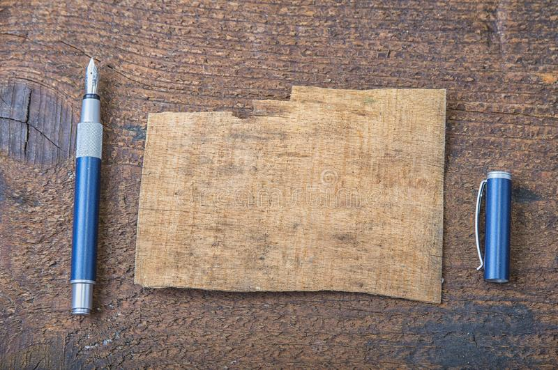 Torn piece of old paper for message or word of wisdom with pen on brown wood stock photo
