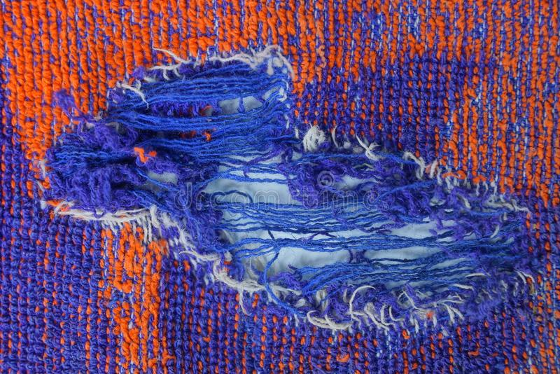 Torn piece of woolen clothes with a hole stock images