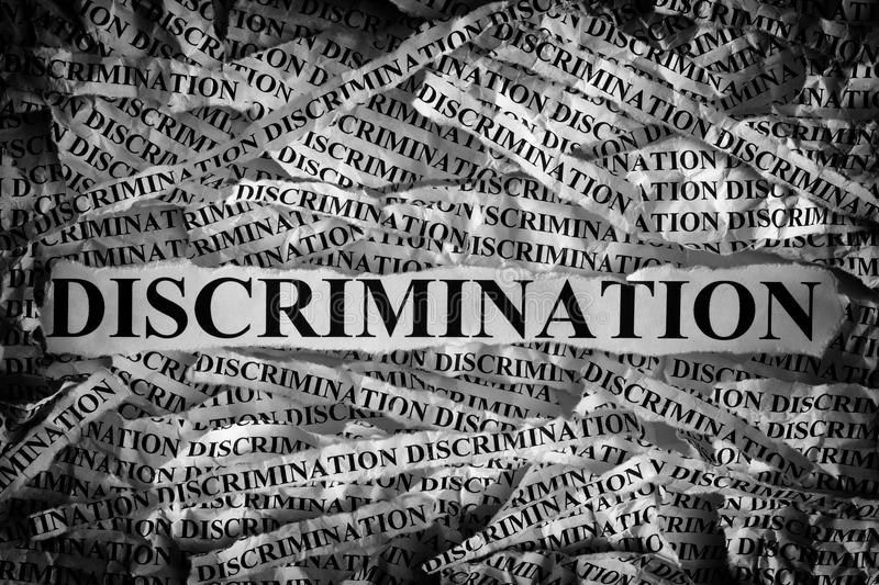 Torn pieces of paper with the word Discrimination stock photos