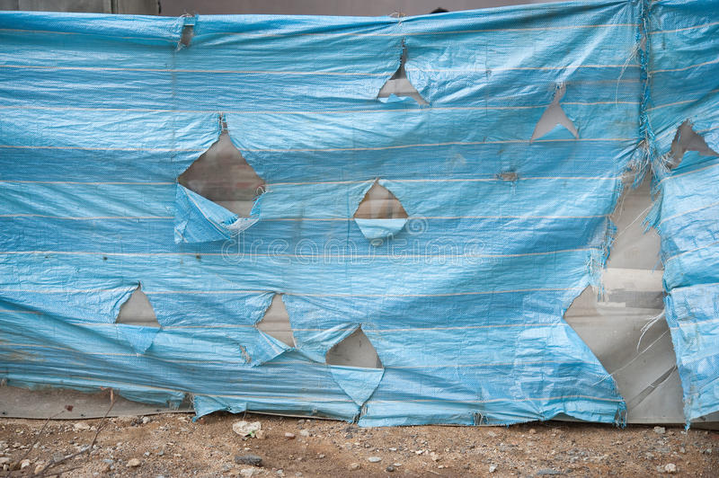 Torn plastic cover. With holes to prevent it from trapping the wind stock images