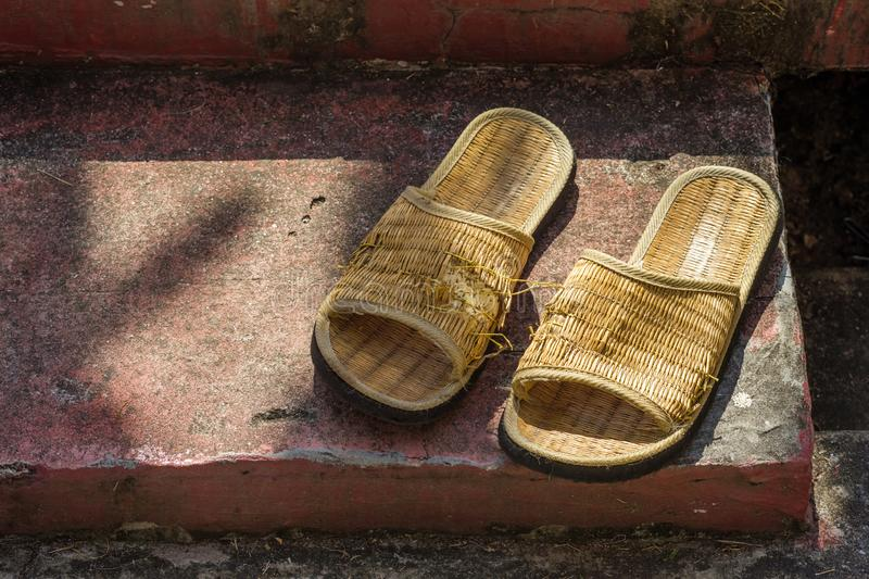 Torn Rattan Flipflop. Pair of handmade woven flipflop on the floor is torn and partly damage royalty free stock photos