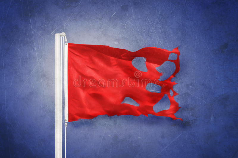 Torn Red flag flying against grunge background.  royalty free stock photography