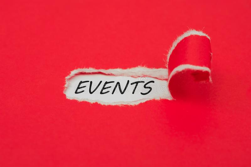 Torn red paper revealing the word events. Upcoming events concept royalty free stock photo
