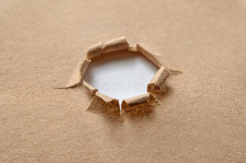 A torn round hole in rough, brown paper stock photo