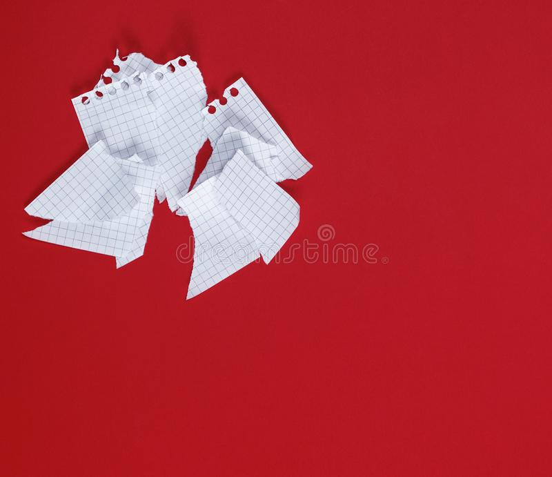 Torn to pieces a white sheet of paper on a red background royalty free stock photography