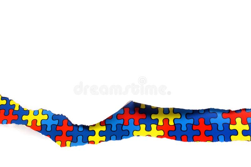 Torn white paper on multicolored puzzle background. Cocept for autism awareness day. Break barriers together for autism. stock images