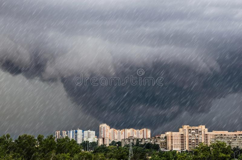 Tornado, funnel clouds during a thunderstorm a heavy rain downpour over the city. royalty free stock photo