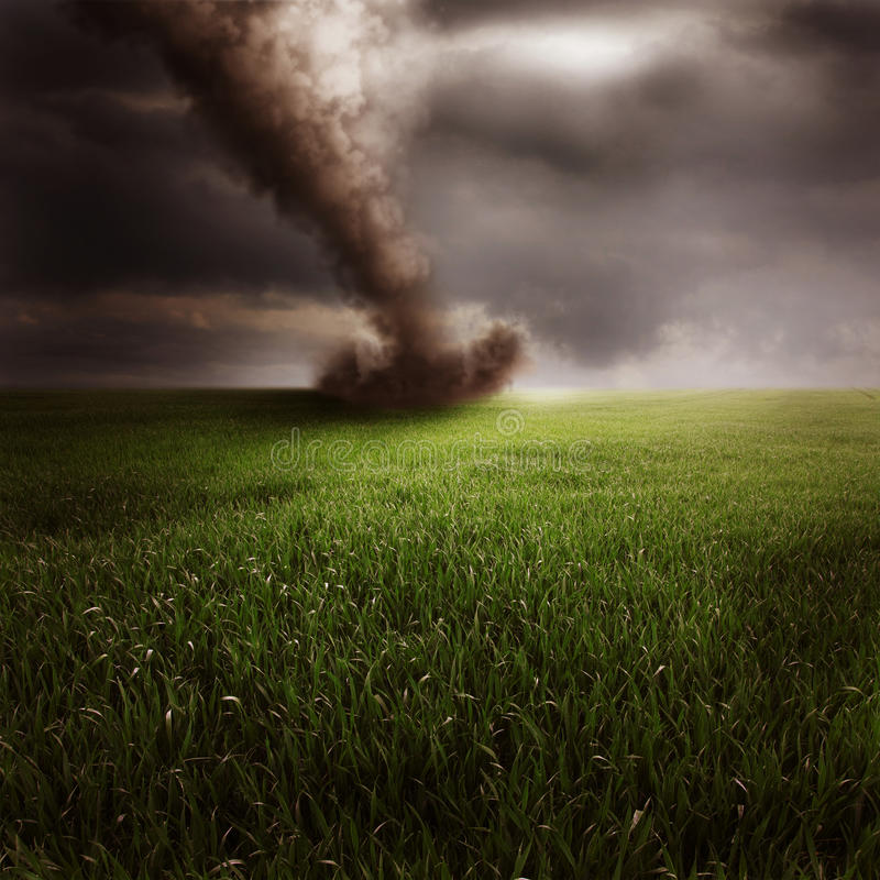 Tornado in green field. Scenic view of tornado in green field with dark cloudscape background stock images