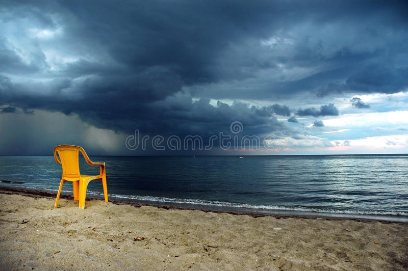 Tornado on the sea. A yellow chair in the foreground stock image