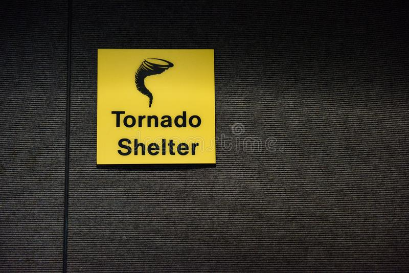 Tornado shelter yellow sign designating a safe room area. With tornado or twister icon stock photos