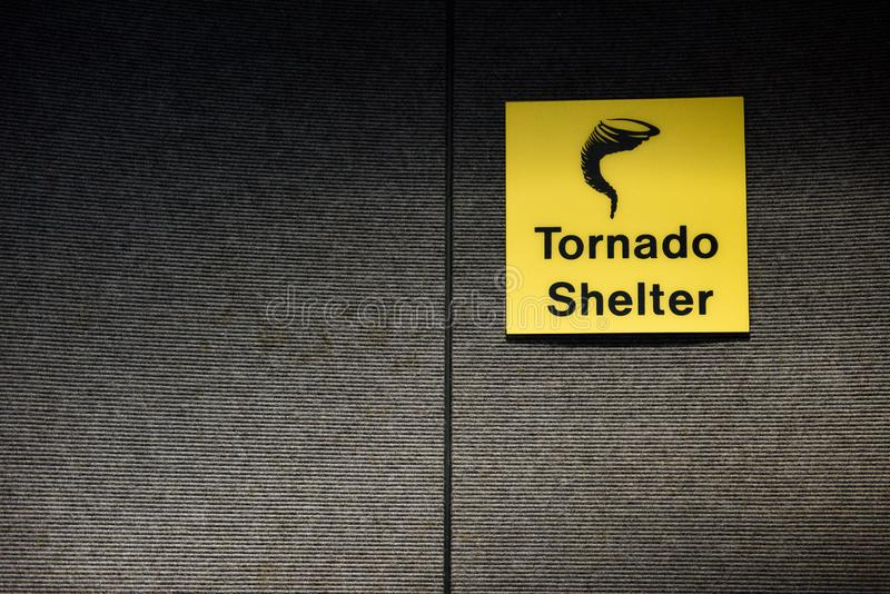 Tornado shelter yellow sign designating a safe room area. With tornado or twister icon royalty free stock photography