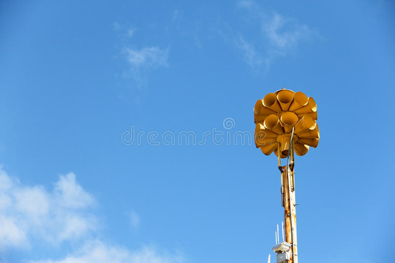 Tornado Siren. Yellow tornado siren enhanced by a gorgeous summer blue sky stock photography