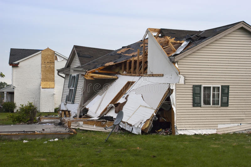 Tornado Storm Damage House Home Destroyed by Wind. Tornado wind and storm wreaks severe damage onto a residential family home. The structure is damaged beyond stock photo