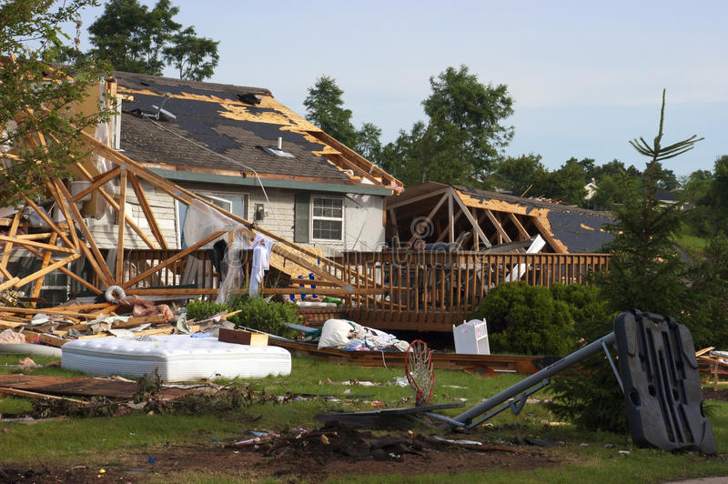 Tornado Storm Damage House Home Destroyed by Wind. Tornado wind and storm wreaks severe damage onto a residential family home. The structure is damaged beyond stock photography