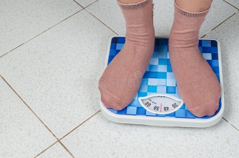 Torne mais pesada a mulher que está em uma máquina de peso retro do estilo imagens de stock