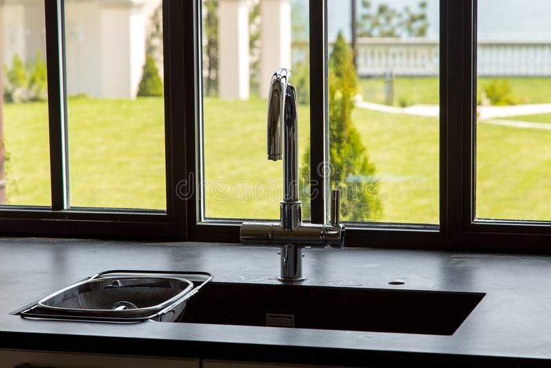 Torneira cromado na banca da cozinha com um tabletop de pedra preto foto de stock