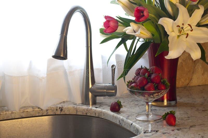 Torneira da cozinha, morangos e flores frescas em um contador. fotografia de stock royalty free