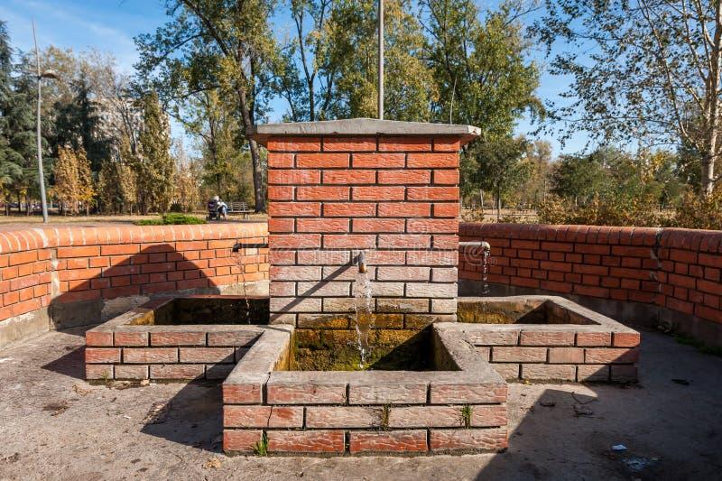 Torneira da fonte bebendo feito de tijolos vermelhos com a água fria fresca que corre para fora da terra da terra foto de stock royalty free