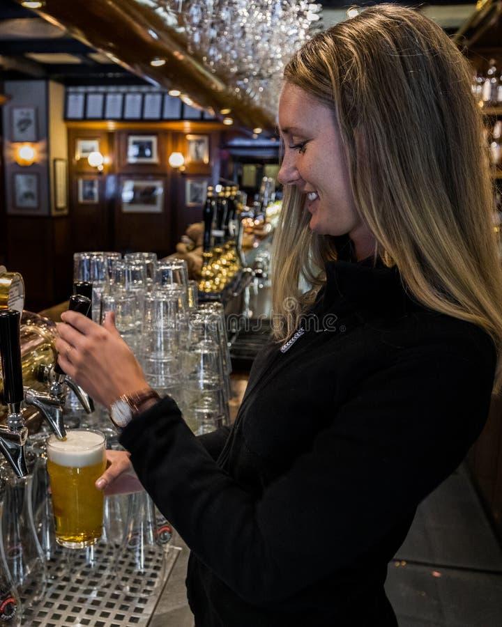 Torneira do barman da mulher um a pinta da cerveja fotografia de stock royalty free