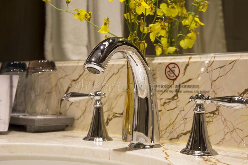 Torneira do torneira do banheiro com artigos dos cosméticos foto de stock royalty free