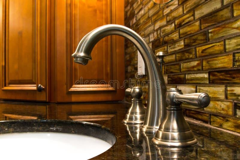 torneira em um banheiro moderno com armários imagem de stock royalty free