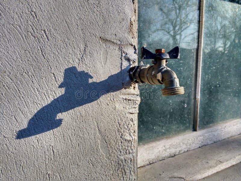Torneira exterior que projeta-se de uma fundação concreta perto de uma janela imagens de stock